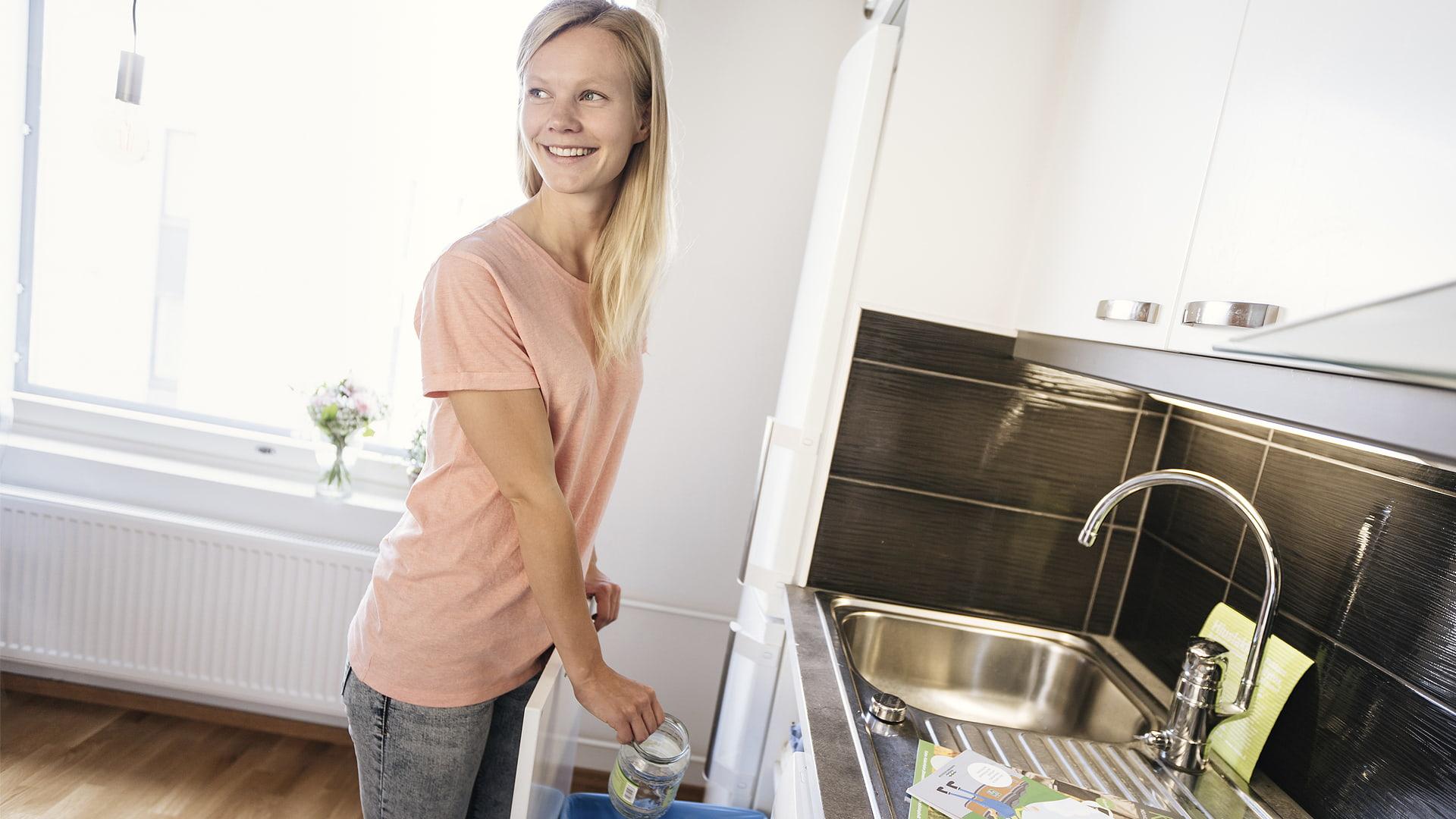 Nainen lajittelmassa jätteitä kotona